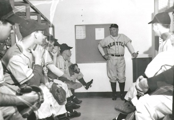 Hall of Famer Rogers Hornsby, standing, addresses the Seattle Mariners during 1951 spring training. K. Chorlton is at the right front, smiling. / David Eskenazi Collection
