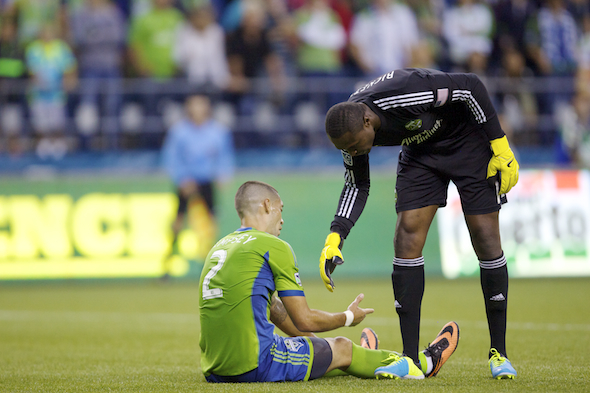 Timbers goalie Donovan Ricketts helps up Clint Dempsey from place he found often Sunday night -- the ground. / Drew Sellers, Sportspress Northwest