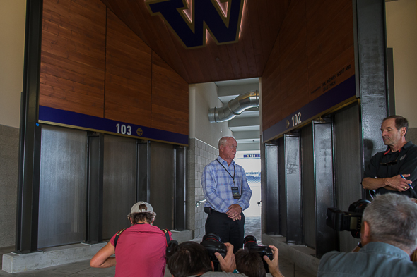 Former Huskies coach Jim Lambright, a member of the stadium renovation committee, pauses the media tour in front of some of the 11 elevators that are a big upgrade from the two in the old barn. / Drew McKenzie, Sportspress Northwest