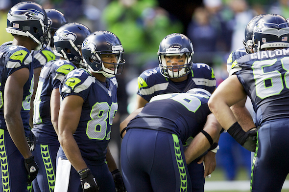 Russell Wilson, in the center, was saddled with a poor passer rating Sunday through no fault of his own, but made several drive-extending plays in leading Seattle to a 23-20 win. / Drew Sellers, Sportspress Northwest