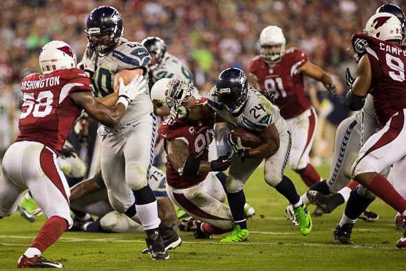 On his way to the end zone, the Seahawks' Marshawn Lynch smashes Arizona DT Darnell Dockett so hard that his helmet took leave of his head. / Drew McKenzie, Sportspress Northwest