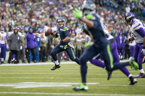 Russell Wilson searches for a receiver during Seattle's 41-20 victory over Minnesota Sunday. Wilson completed 13 passes but had a 154.3 passer rating. / Drew McKenzie, Sportspress Northwest
