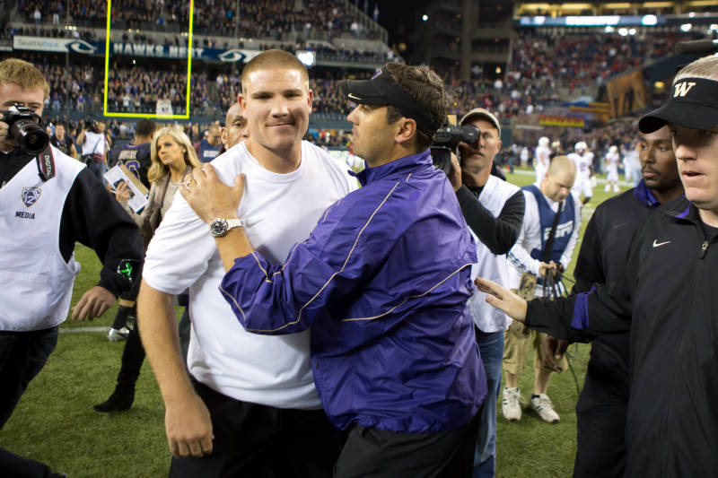 Tosh Lupoi still has his job coaching Washington in its bowl game as the school investigates allegations of recruiting improprieties. / Gohuskies.com