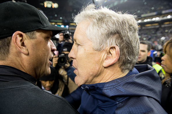 "Carroll and Harbaugh put behind them the ""What's Your Deal"" incident with a post-game hug and handshake at midfield. / Drew McKenzie, Sportspress Northwest"