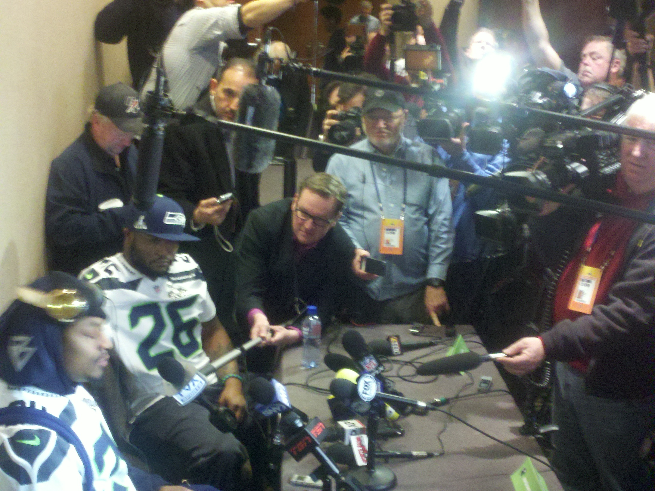 Marshawn Lynch, left, and teammate Michael Robinson face the media horde Wednesday at the team's hotel in Jersey City, N.J. / Art Thiel, Sportspress Northwest