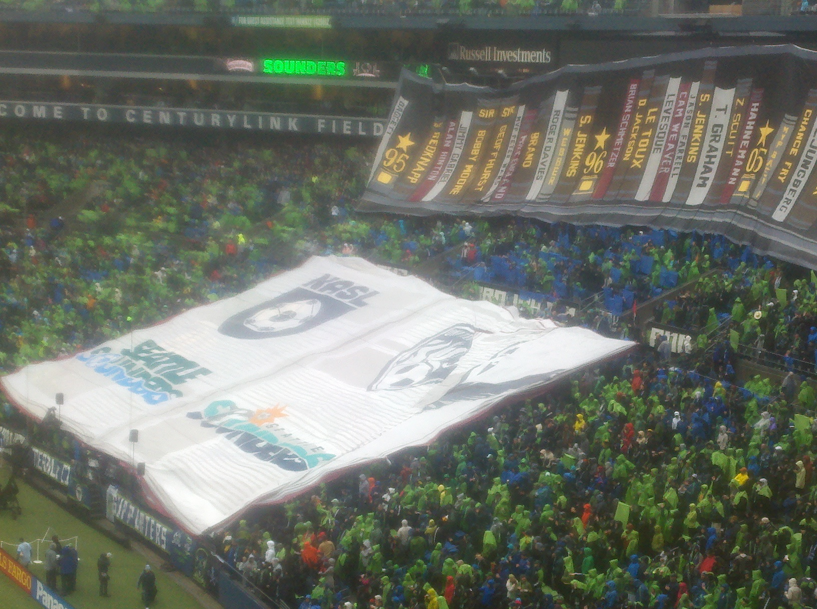 "The Emerald City Supporters' massive tifo, showing the versions the logo through 40 years of pro soccer in Seattle, was unveiled in pre-game. A second ""page"" was opened after the cover was pulled back. / Art Thiel, Sportspress Northwest"
