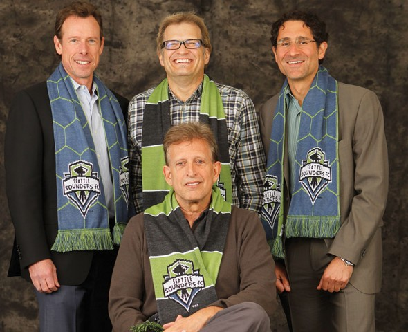 Peter McLoughlin, left, is Seahawks CEO. Drew Carey, Adrian Hanauer and Joe Roth (seated) are taking the Sounders to their own shop. / SoundersFC.com