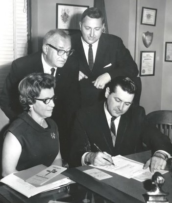 Johnny O'Brien (seated), the former Seattle U. basketball and major league player, became a King County Commissioner following his athletic career and advocated for a domed stadium. He is shown here with Mrs. Ludwig Lobe and fellowcCommissioners Ed Munro (back, left) and John Spellman in 1967. Spellman later became King County Executive. / David Eskenazi Collection