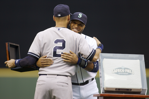 Derek Jeter gets a hug and an inscribed watch from former teammate Robinson Cano Tuesday night at a Safeco Field ceremony honoring the career of the Yankee captain. / Drew Sellers, Sportspress Northwest